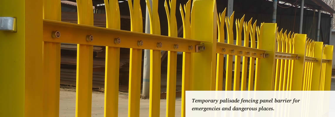 Yellow powder-coated palisade fencing panels used as temporary security fence.