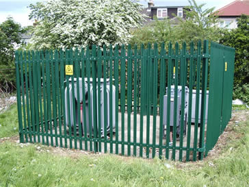 A transformer surrounded by palisade fencing.