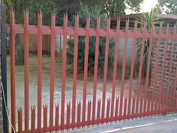 Red palisade single gate for a house.