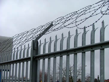 High security metal palisade fencing with razor wire on the top.