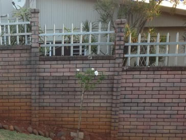 White palisade fencing with height less than 1 meter installed on the wall.